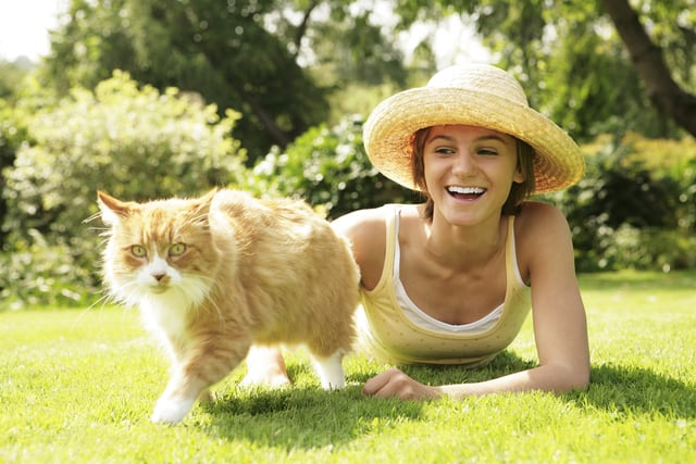 Woman laying on the grass with her cat