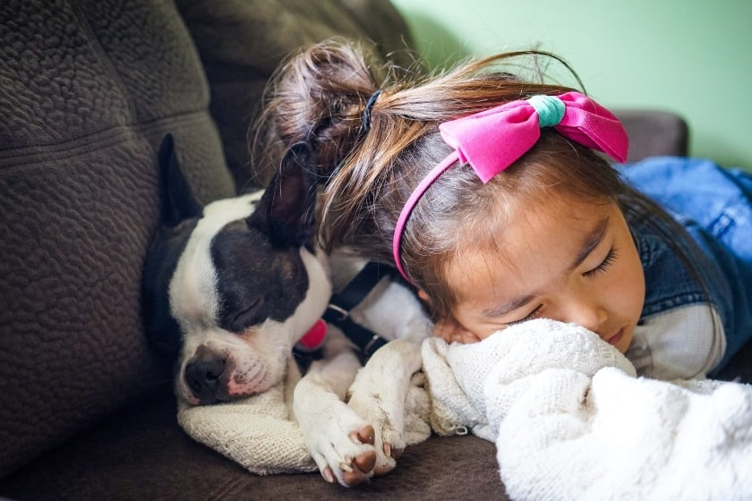 Little girl and her pup eyes closed