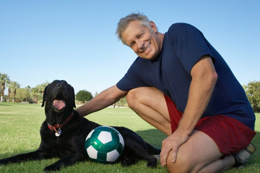Senior and his black dog outside at soccer ball park