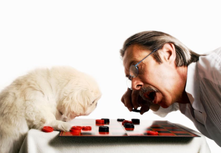 Senior playing checkers with his dog